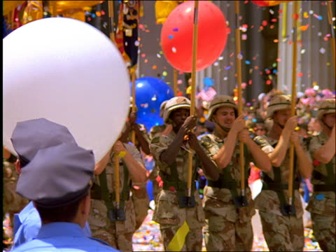 slow motion soldiers carrying flags in ticker tape parade / tilt up / Operation Welcome Home / NYC