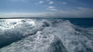 Slow motion speed boat wake tropical island horizon