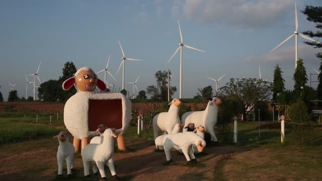 Slow Motion statues of sheep stand in front of wind turbines outside the Subplu wind farm operated by Gunkul Engineering Pcl in Huay Bong Thailand on...