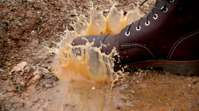Slow motion The Boot Stomping in a rain puddle making splash