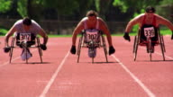 slow motion three men in wheelchairs racing toward camera on track