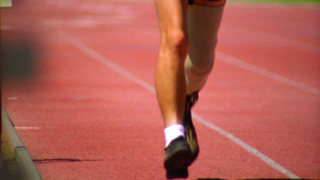 slow motion tilt down Hispanic man running with prosthetic leg toward camera on track