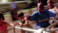CANTED slow motion time lapse children raising arms + laughing on merry-go-round with girl pushing / Florida