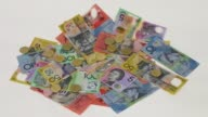 Slow Motion tossed one dollar coins bounce over Australian dollar banknotes of various denominations arranged for video in Sydney Australia on Friday...