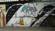 Slow motion tracking shot of graffiti art on perimeter wall of a building in Rio de Janeiro, Brazil