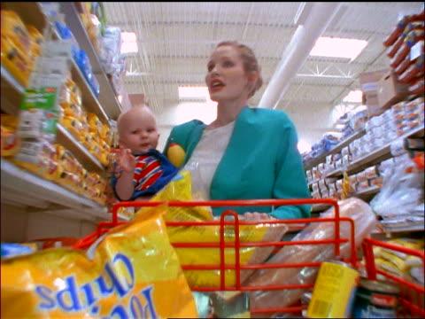 slow motion tracking shot stressed businesswoman holding baby + pushing cart thru aisle of supermarket