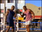 slow motion two Black men doing biceps curls with dumbbells outdoors / Muscle Beach, California