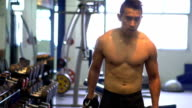 Slow Motion Video : Handsome young man lifting weights in the gym