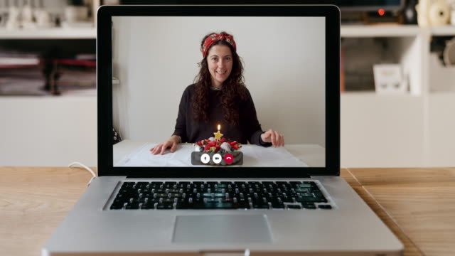 Slow motion video of a laptop with a woman and her birthday cake on the screen