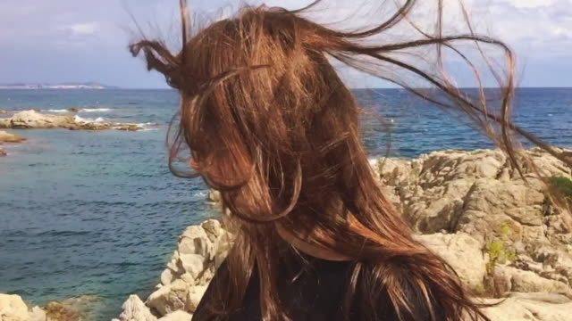 Slow motion view of a woman in the Mediterranean Sea Costa Brava shoreline on summer with sunny day and the wind playing with his long hair.