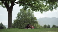 Slow motion view of dad and daughter under tree reading a book.