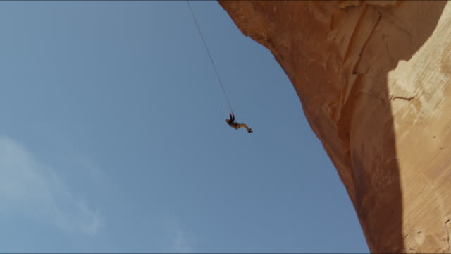 Slow motion wide panning shot of man swinging from arch / Corona Arch, Moab, Utah, United States