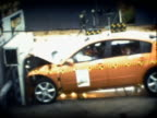 Slow motion wide shot 35mph frontal barrier impact test on 2004 four-door Nissan Maxima with crash test dummies