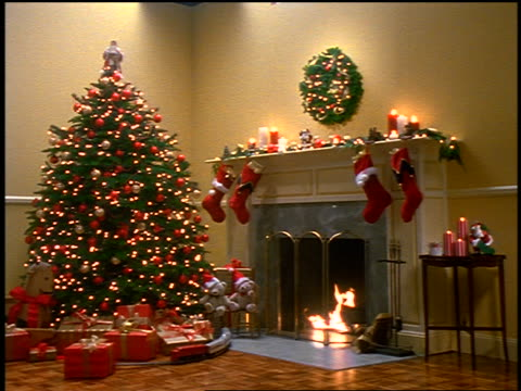 slow motion wide shot Christmas tree with gifts underneath next to fireplace with hanging stockings in living room