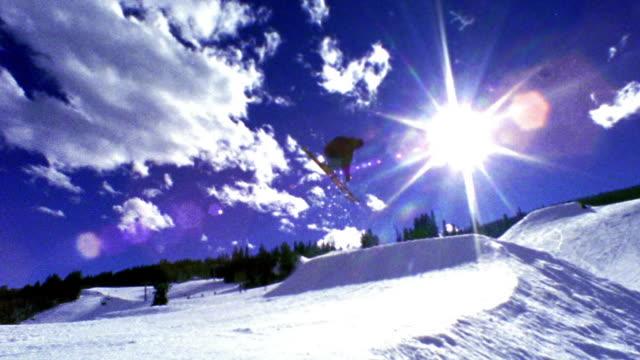 slow motion wide shot PAN man skiing off ramp, flying high in air turning + flipping / Aspen, Colorado