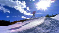 slow motion wide shot PAN man skiing off ramp, flying high in air turning + flipping / Aspen, Colorado