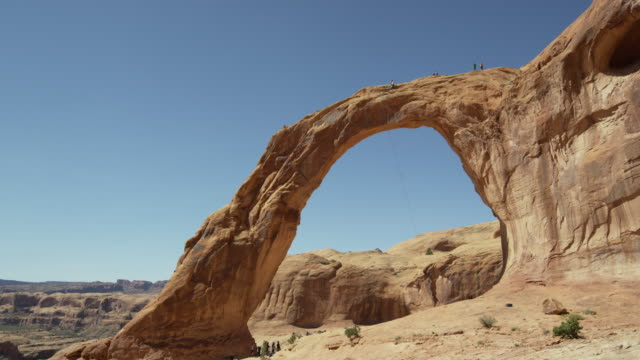 Slow motion wide shot of people watching man swinging from arch / Corona Arch, Moab, Utah, United States
