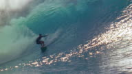 Slow motion wide shot pan male sufer riding inside large wave and toward beach / Oahu, Hawaii