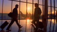 Slow motion wide shot silhouetted people walking past windows at sunrise or sunset in airport