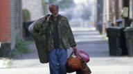 Slow motion wide shot tilt up homeless man carrying several bags / walking on sidewalk