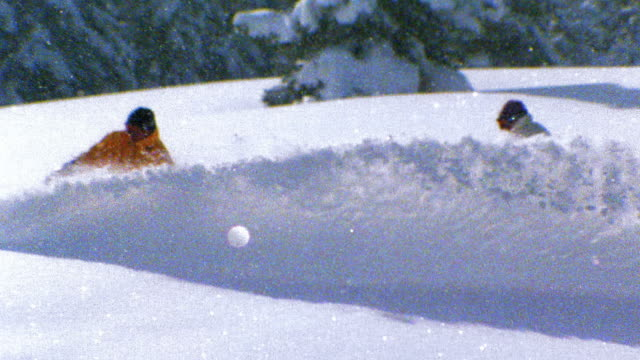 Slow motion wide shot tracking shot two people snowboarding on mountain slope and spraying snow / Aspen, Colorado