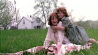 Slow motion wide shot young redheaded girl hugging and kissing second girl sitting on blanket / they fall back /MO
