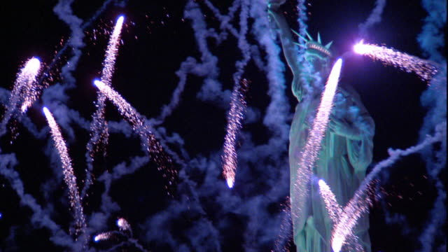 Slow motion wide shot zoom in to medium shot fireworks shooting into sky around Statue of Liberty / New York City