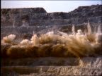 slow motion wide shot zoom out of explosion in hillside at strip mine / Brazil