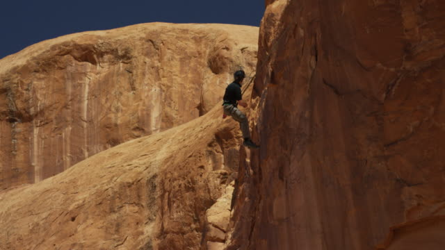 Slow motion wide tracking shot of man swinging from arch / Corona Arch, Moab, Utah, United States