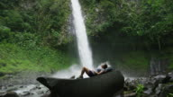 Slow motion wide zoom in of hiker laying on rock formation near rain forest waterfall / Arenal, La Fortuna, Costa Rica
