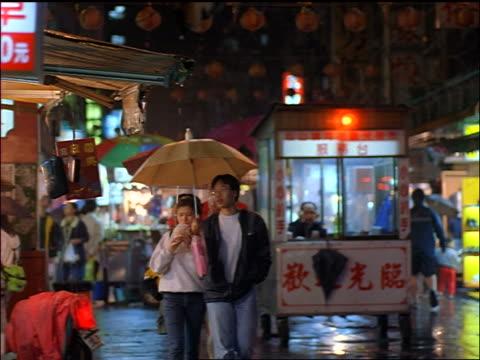 slow motion young Asian couple walking under umbrella on city sidewalk / Night Market, Taipei, Taiwan