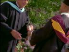 slow motion young Black man receiving diploma at graduation ceremony + holds it up in the air