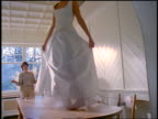 slow motion young blonde woman walking on dining room table modelling wedding dress for mother