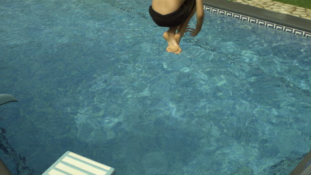Slow motion young boy bombing into swimming pool, Spain (Individual frames may also be used as a still image. Each frame in its raw state is about 6MB or about 12MB as a 16 bit TIFF)