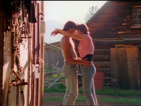 slow motion zoom in couple in blue jeans hugging in doorway of barn / Montana