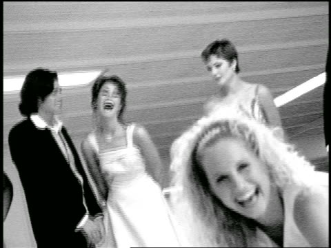 B/W slow motion zoom in + zoom out bridesmaids + ushers laughing at blonde bride preparing to bowl in alley