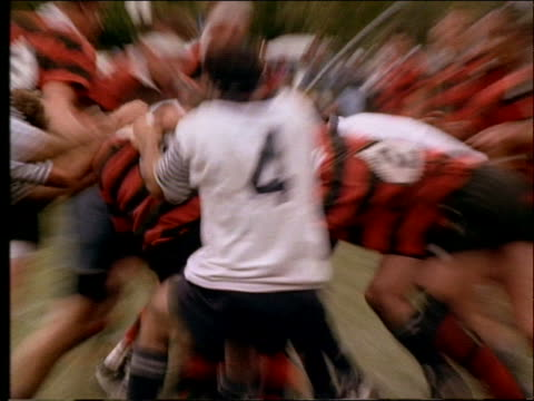 slow motion zoom in + zoom out of players tackling in rugby match