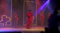 slow motion zoom in zoom out time lapse man singing on stage with female dancers behind him