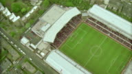 AERIAL slow motion zoom out from stands to soccer stadium during game / zoom in + zoom out from field / Arsenal FC, London