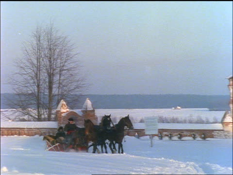 slow motion zoom out PAN horses + sleigh going by country monastery in snow / Zagorsk, Russia