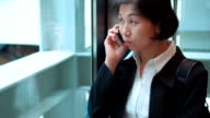 Slow Motion,Businesswoman using smartphone  in elevator,shopping mall