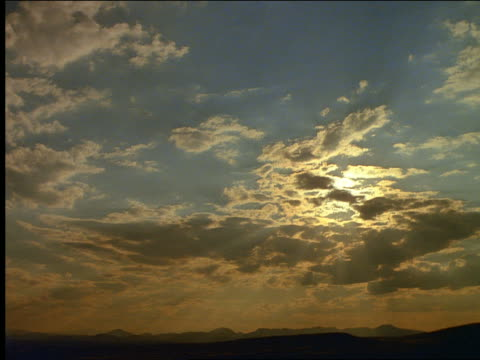 Slow moving clouds at sunset over mountains