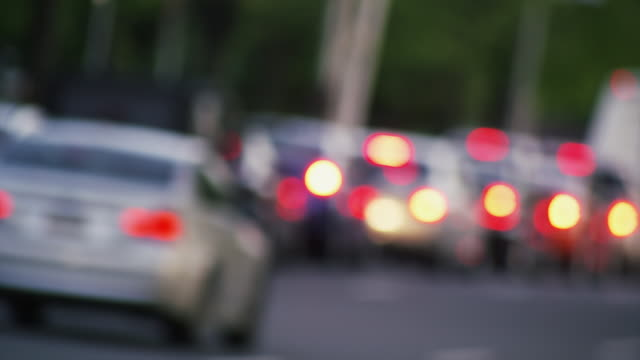 Slow moving commuter traffic congestion, cars travel away from camera.