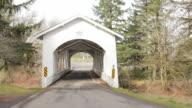 Slow pan across bridge entrance in rural country setting.