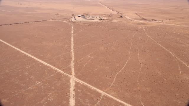 Slow reveal of desert storage tank/refining operation