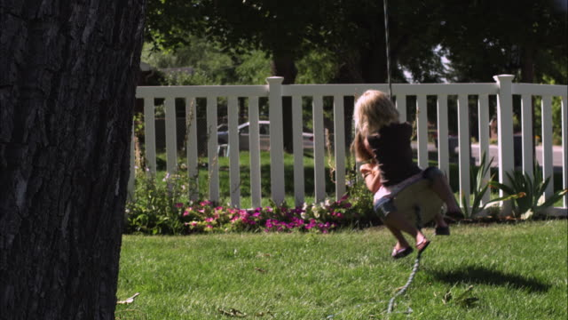 Slow satic shot of two little girls riding a tree swing