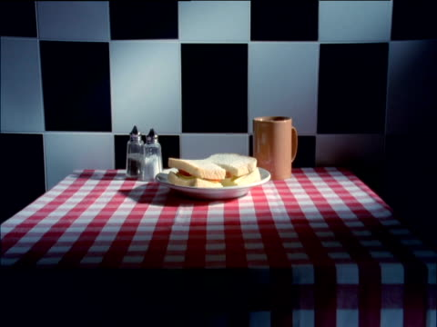 Slow track forward over cheese and tomato sandwich mug of tea salt and pepper pots on table to black and white tiles on wall