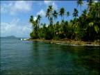 Slow track over calm blue sea idyllic palm tree lined coast blue sky with clouds Panama