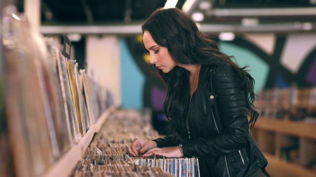 A slow track to reveal a woman shopping in a record store.