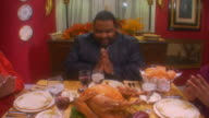 Slow zoom in on a man praying before eating a Thanksgiving meal